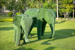 Giant animal sculptures made from grass.