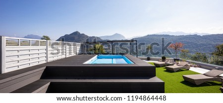 Giant balcony of modern apartment with swimming pool on a summer day. Nobody inside