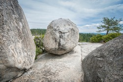 Giant boulders on rugged barren rocky mountain under blue cloudy sky