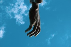Giant bronze metal hand suspended in the blue cloudy sky