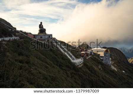 Giant buddha statue on top of Fansipan mountain peak, Backdrop Beautiful view blue sky and cloud in Sapa, Vietnam. Buddha statue on top at sunset in the clouds.