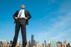 Giant businessman standing tall in dark suit above the city skyline