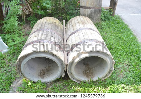 Giant concrete water pipes on the evergreen lawn beside the house outdoor being prepared for the construction to help make effective drainage system and protect flooding problem Stock fotó ©