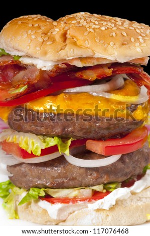 Giant double hamburger with tomato slices, cheese, cream cheese, bacon, egg, lettuce and onion in a white bread bun