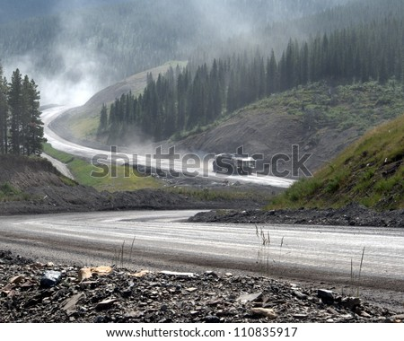 stock photo : Giant dump truck makes it way down from an open pit coal mine