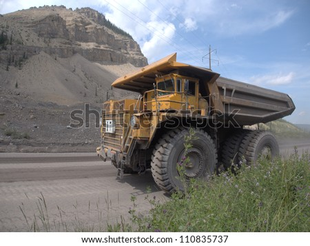 Giant dump truck makes it way into the Canadian Rocky Mountains near an open pit coal mine
