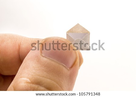 Giant fingers holds little open envelope with a letter inside