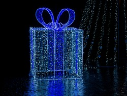 Giant gift box with bow illuminated with Christmas lights.
