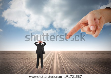 Giant hand pointing at businessman standing back to the camera with hands on head against cloudy sky background