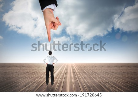 Giant hand pointing at businessman standing back to the camera with hands on hips against cloudy sky background