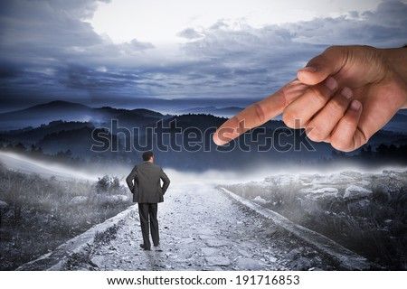 Giant hand pointing at businessman with hands on hips against stony path leading to large misty mountains