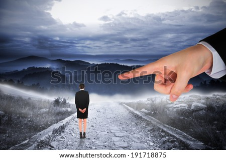 Giant hand pointing at businesswoman standing with hands behind back against stony path leading to large misty mountains