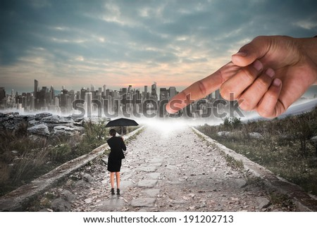 Giant hand pointing at young businesswoman holding umbrella against stony path leading to large city on the horizon