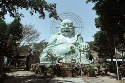 Giant laughing and sitting buddha statue in turquoise color at a Mahayana buddhist temple called Linh An Pagoda in Dalat, Vietnam