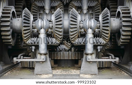 Giant mechanical cast iron gear in a congested industrial engine chamber.