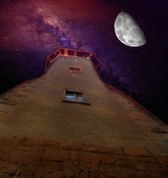 Giant moon and stars of bright Milky Way viewed over old European tower shot from low angle. Space fantasy concept