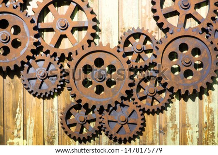 GIANT OLD AND RUSTY COGWHEELS ON THE WALL