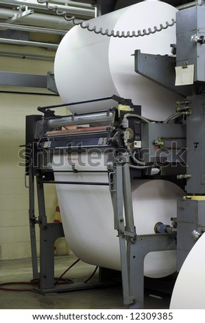Giant paper rolls on a web press in a publishing company