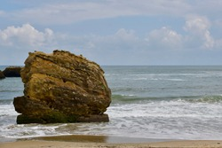 Giant rock in the sea. Landscape of a beach with waves breaking on a big rock. Biarritz french Basque Country in southwestern France.