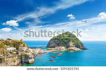 Giant rock with green trees on top near small village Sant'Angelo on Ischia island, Italy