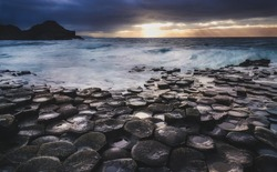 Giant's Causeway, North Ireland, UK (Winter) Fierce waves batter the iconic coastline of North Ireland during a storm. In the distance, sunrays are released as the storm clouds start dispersing.