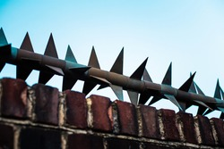 Giant spikes on top of a brick wall. Gives a trapped and imprisoned feel