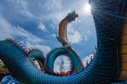 Giant Thai Naga Statue with sunray on  blue sky clouds in the Phu Manorom Temple, Statue of Naka Buddha and White large Buddha statue at Mukdahan Province, Thailand.