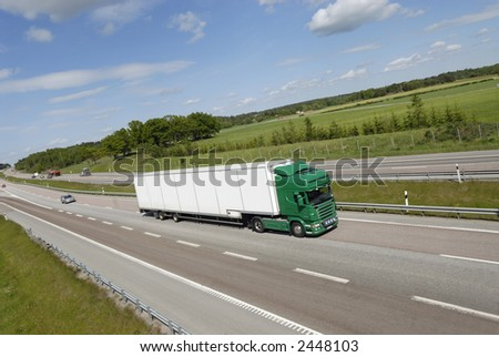 giant truck, lorry, in clean surrounding driving on freeway