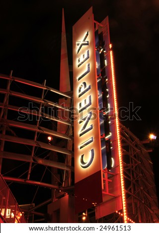 Giant vertical neon sign advertising movie theater
