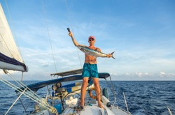 Giant Wahoo (spanish mackerel, king fish) trolling on a sailing yacht. Happy fisherman in shorts with his trophy on background of white boat deck. Fishing in Indian ocean near Phuket island, Thailand