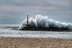 Giant waves breaking on the breakwater and the lighthouse on Aguda Beach, Miramar, Arcozelos town