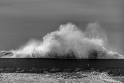 Giant waves breaking on the breakwater on Aguda Beach, Miramar, Arcozelos town