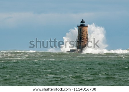 Giant waves cover the stone tower of Whaleback lighthouse in southern Maine during an astronomically high tide. #1114016738