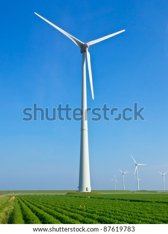 Giant wind turbine in dutch agricultural landscape