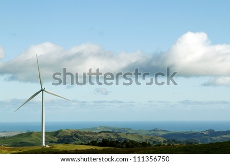 Giant wind turbine on hill. Coastline in background