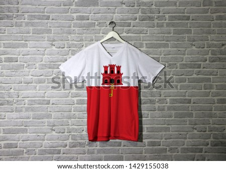 Gibraltar flag on shirt and hanging on the wall with brick pattern wallpaper, white and red stripe with three towered and hangs a gold key.