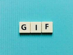 GIF word made from square letter tiles on turquoise background.