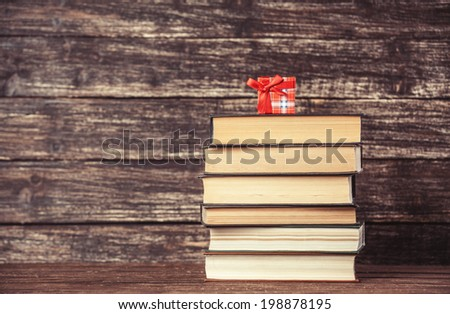 Gift and books on wooden table.