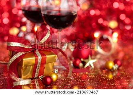 Gift and wine for holidays against blurred lights.
