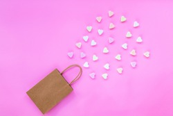 Gift bag with scattered hearts sweets on a pink background. Valentine's Day present concept. Top view, flat lay.
