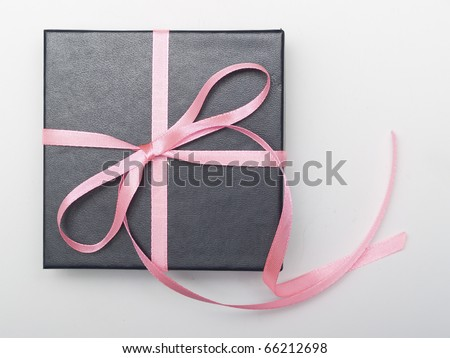 Gift black box tied with satin ribbon on gray
