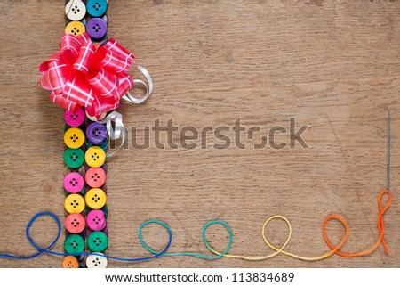 Gift bow, colorful buttons, thread with needle on wooden textured background