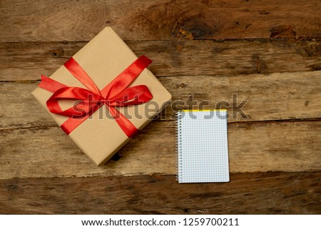 Gift box and blank notebook on wood table vintage background and copy space in Anniversary wish list New Year Resolutions Christmas Celebration San Valentine day and best wishes design card concept. #1259700211