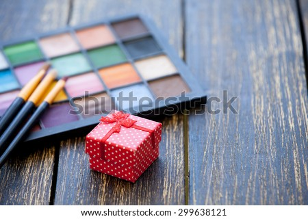 Gift box and brushes for makeup with palette on wooden table.