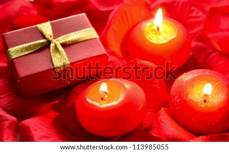 gift box and candle on rose petals - stock photo