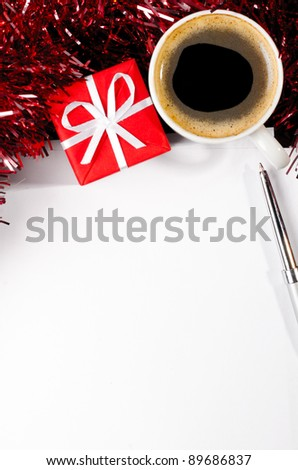 gift box and coffee cup with paper sheet on dark table