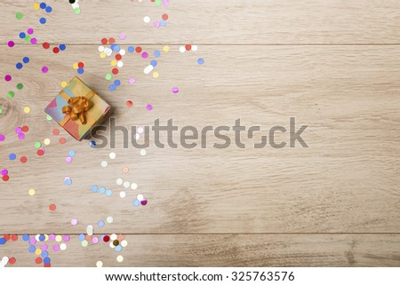 Gift box and colorful confetti on a wooden background