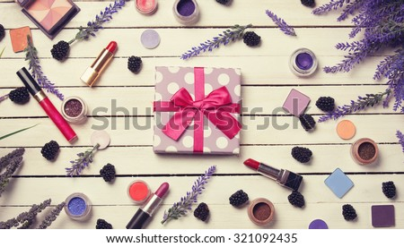 Gift box and cosmetics on white wooden table.