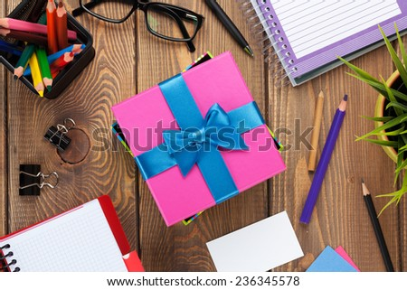 Gift box and office supplies over office table. View from above