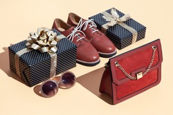 Gift box and stylish clothes on beige background. Minimal isometric design. Holidays and shopping concept